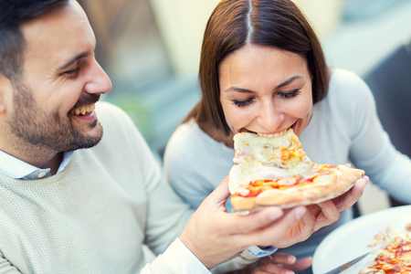Foto de Couple eating pizza snack outdoors.They are sharing pizza and eating. - Imagen libre de derechos
