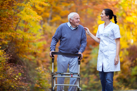 Photo pour Nurse helping elderly senior man. Senior man using a walker with caregiver outdoor - image libre de droit