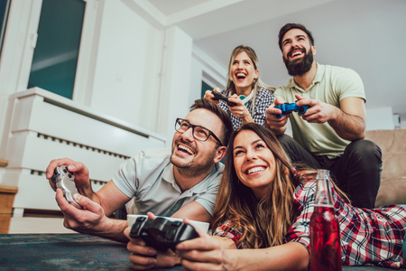 Photo for Group of friends play video games together at home, having fun. - Royalty Free Image