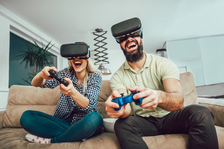 Photo pour Happy friends playing video games with virtual reality glasses - Young people having fun with new technology console online - image libre de droit