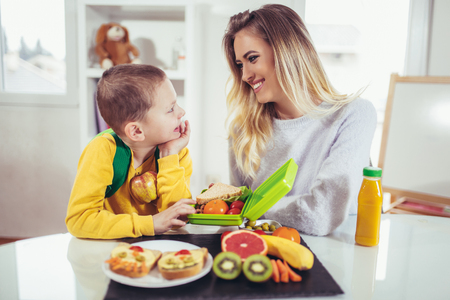 Foto per Mother making breakfast for her children in the morning and a snack for school - Immagine Royalty Free