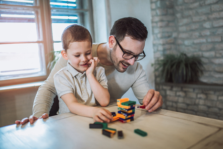 Foto de Father and adorable son playing with education game, family fun at home concept - Imagen libre de derechos