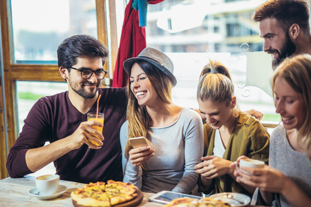 Photo for Young friends sharing pizza in a indoor cafe - Royalty Free Image