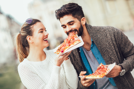 Photo for Couple eating pizza outdoors and smiling. - Royalty Free Image