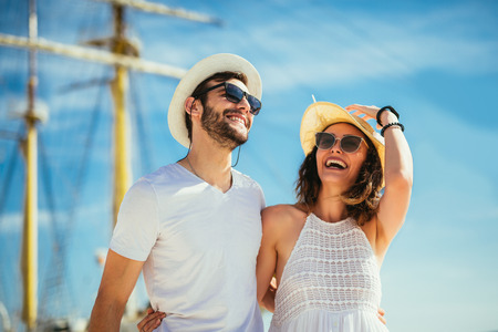 Photo pour Happy young couple walking by the harbor of a touristic sea resort with sailboats on background - image libre de droit