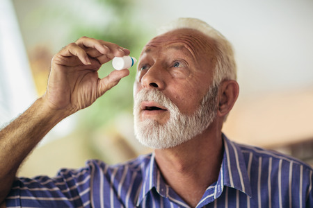 Foto de Elderly Person Using Eye Drops - Imagen libre de derechos