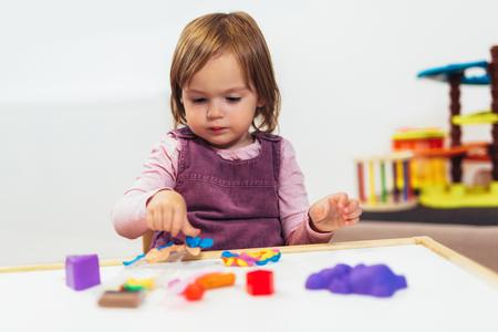 Foto de Kid girl is playing with plasticine while sitting at table in nursery room. - Imagen libre de derechos