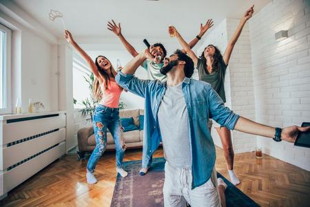 Foto de Group of friends playing karaoke at home. Concept about friendship, home entertainment and people - Imagen libre de derechos