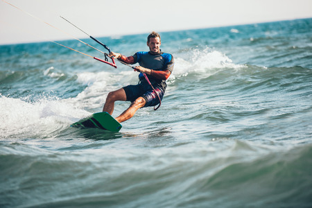Photo pour Professional kiter makes the difficult trick on a beautiful background. Kitesurfing Kiteboarding action photos man among waves quickly goes - image libre de droit