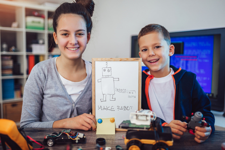 Foto de Happy smiling boy and girl constructs technical toy and make robot. Technical toy on table full of details - Imagen libre de derechos