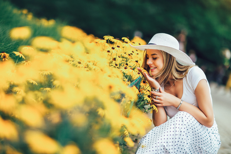 Foto de Beautiful young woman smelling yellow flower in the park. - Imagen libre de derechos