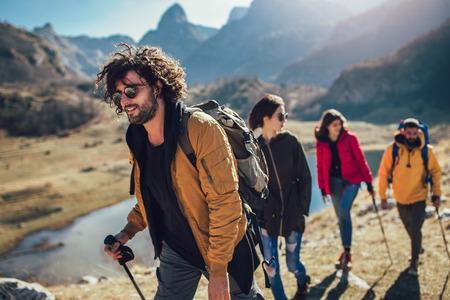 Foto de Group of hikers walking on a mountain at autumn day - Imagen libre de derechos