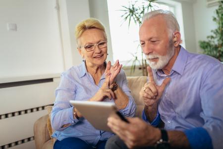 Photo pour Smiling deaf senior couple talking using sign language on the digital tablet's cam - image libre de droit