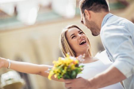 Photo pour Picture of young man surprising woman with flowers - image libre de droit