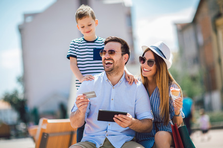 Photo for Smiling parents and little boy with tablet pc and credit card outdoor - Royalty Free Image