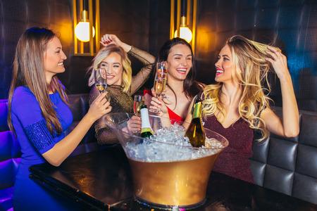 Foto de Happy women clinking champagne glasses and celebrating at night club - Imagen libre de derechos