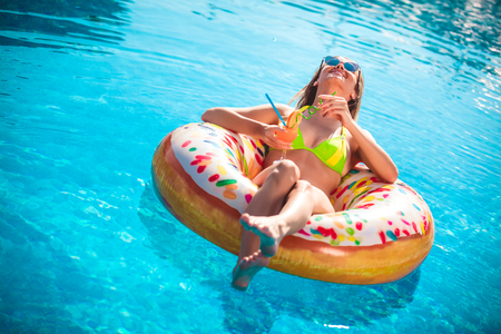 Photo pour Summer Vacation. Enjoying suntan Woman in bikini on the inflatable mattress in the swimming pool. - image libre de droit
