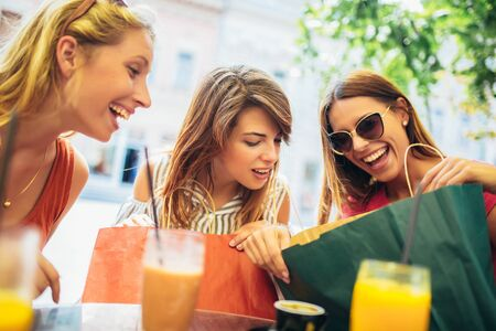 Photo pour Three young women in a cafe after a shopping - image libre de droit