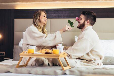 Foto de Young happy couple having breakfast in luxury hotel room.  - Imagen libre de derechos