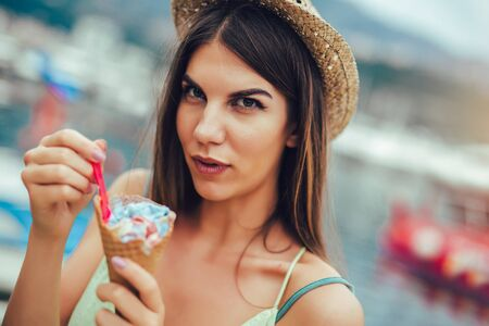 Photo for Woman eating ice cream outside on summer vacation in holiday beach resort. - - Royalty Free Image