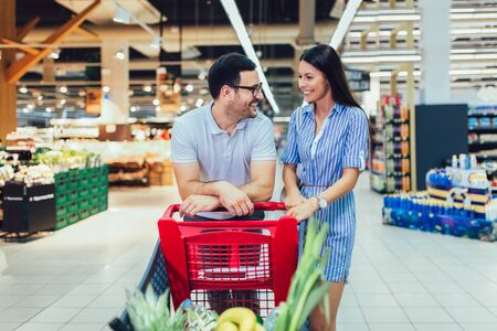 Foto de Happy young couple bonding to each other and smiling while walking while walking in food store with shopping cart - Imagen libre de derechos