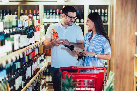 Photo pour Happy couple shopping in supermarket buying wines - image libre de droit