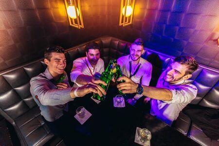 Foto de Group of young men toasting at a nightclub - Imagen libre de derechos