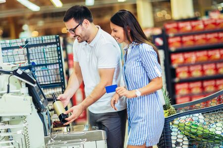 Photo pour Couple with bank card buying food at grocery store or supermarket self-checkout - image libre de droit