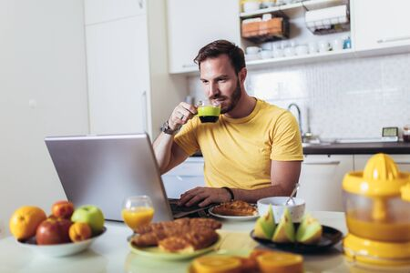 Photo for Busy man working at home, using laptop while having breakfast. - Royalty Free Image