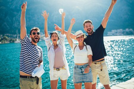 Photo pour Happy group of tourists traveling and sightseeing together near the sea - image libre de droit