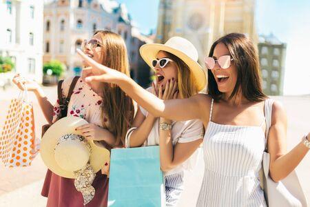 Foto de Three beautiful girls in sunglasses with shopping bags in city. - Imagen libre de derechos