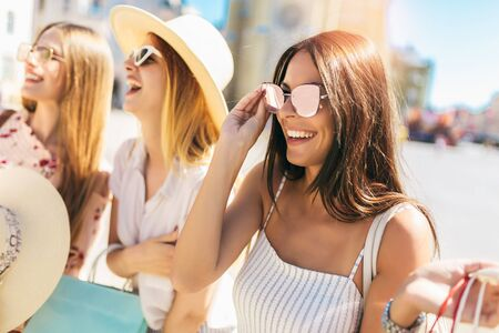 Photo for Three beautiful girls in sunglasses with shopping bags in city. - Royalty Free Image