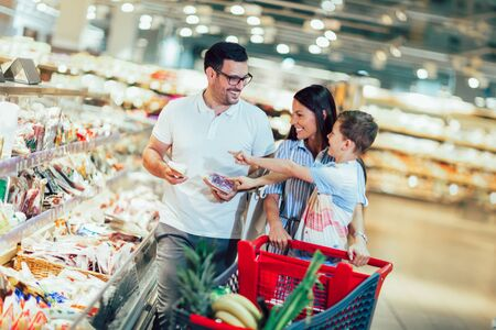 Photo pour Happy family with child and shopping cart buying food at grocery store or supermarket - image libre de droit