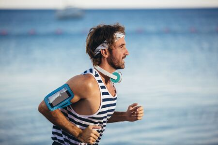 Photo for Running man jogging on beach. Male runner training outside working out. - Royalty Free Image