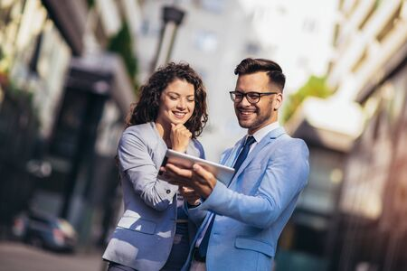 Photo for Handsome man and beautiful woman as business partners using digital tablet outdoor - Royalty Free Image