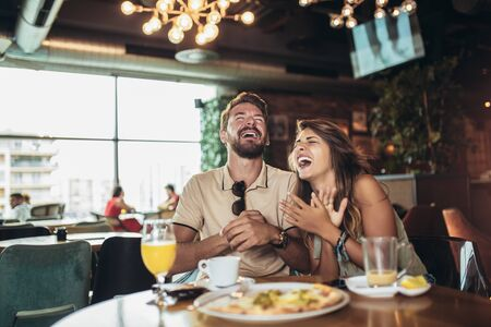 Photo pour Shot of a young happy couple eating pizza in a restaurant and having fun. - image libre de droit