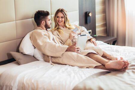 Photo pour Young happy couple shopping online in luxury hotel room. - image libre de droit