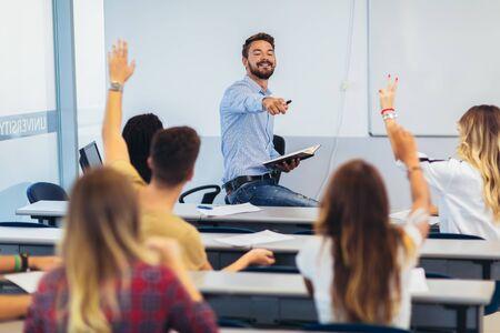 Foto de Group of students raising hands in class on lecture - Imagen libre de derechos
