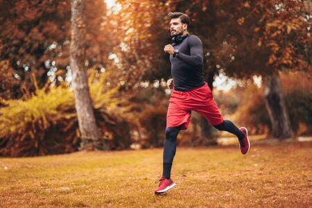 Photo pour Young man running at park during autumn morning - image libre de droit