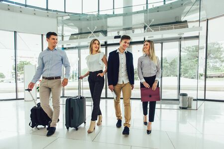 Photo pour Business people talk and walk together with digital tablet tablet and luggage. - image libre de droit