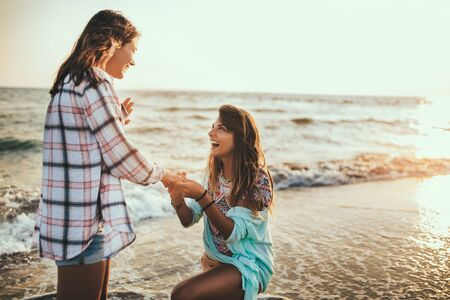 Photo for Woman proposing to her happy girlfriend on the beach - Royalty Free Image