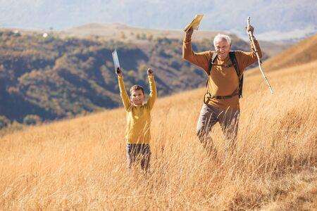 Photo pour Senior man with grandson on country walk in autumn. - image libre de droit