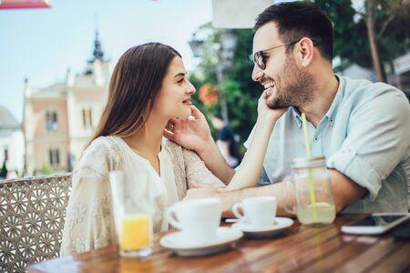 Foto de Beautiful loving couple sitting in a cafe enjoying in coffee and conversatio - Imagen libre de derechos