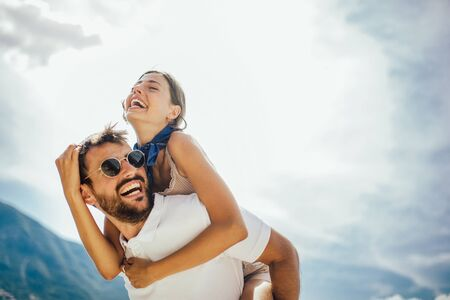 Photo for Handsome young man giving piggyback ride to girlfriend on beach. Romantic young couple enjoying summer holidays.  - Royalty Free Image