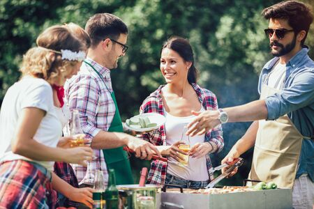 Photo pour Group of people standing around grill, chatting, drinking and eating. - image libre de droit