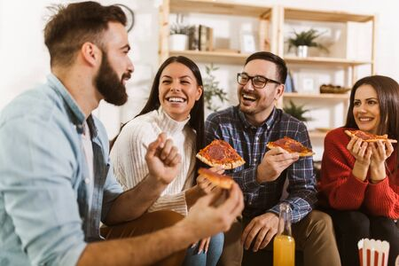 Photo for Group of young friends eating pizza in home interior.  Young people having fun together.  - Royalty Free Image