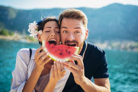 Foto de Young smiling couple eating watermelon on the beach having fun - Imagen libre de derechos