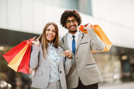 Photo for Couple in shopping. Happy couple with shopping bags and credit card enjoying in shopping. - Royalty Free Image