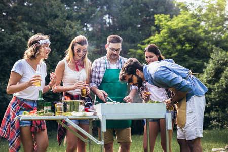 Photo pour Friends having fun grilling meat enjoying bbq party - image libre de droit
