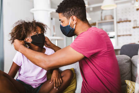Photo pour Father in a medical mask puts a protective mask on his daughter at home.Kid safety after coronavirus pandemic. - image libre de droit